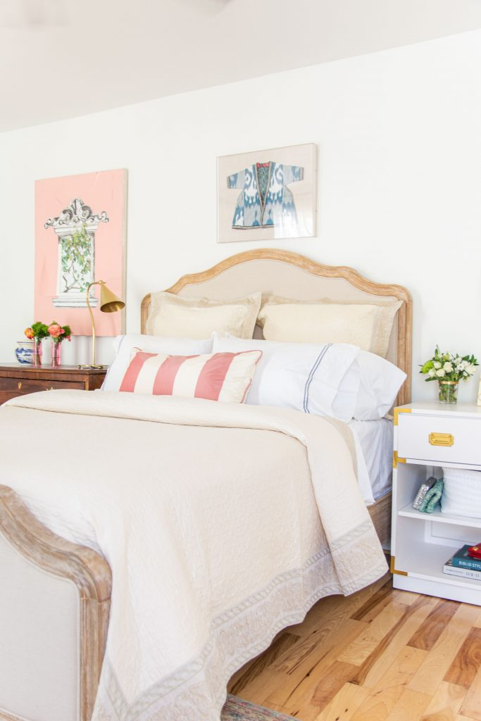 Master bedroom ideas, cream bedding with pink accents, upholstered bedframe with white nightstands, how to set bed by Kevin O'Gara on Thou Swell #bedroom #bedding #bedroomdesign #beddesign #settingabed #homedecorideas