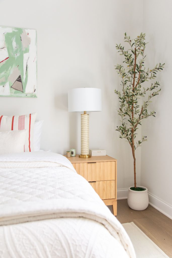 Guest room bedroom design with pale grey walls, abstract painting, faux olive tree, and striped area rug by Kevin O'Gara on Thou Swell #bedroom #guestroom #guestbedroom #bedroomdesign #interiordesign #homedesign #homedecorideas