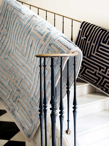 Blue luxury area rug hanging over stair banister by Kevin Francis Design