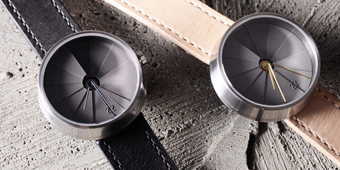 A duo of 22 Design watches laid on a concrete background