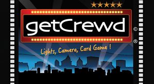 getCrewd Party Card Game lead photo on website showing a city at night with big spotlights and a theater marquee.  LIghts, Camera, Card Game !