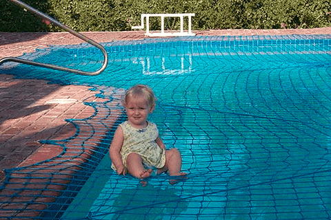 baby sitting on a safe pool net