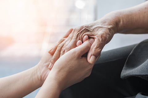 Young hand holding an elderly hand, pain management