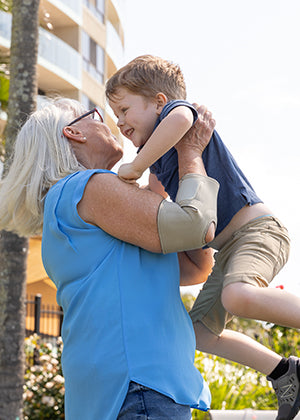 Grandmother holding her grandson while wearing the BioMagnetic Elbow Support in Beige.