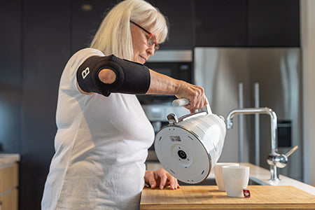 Elderly Woman pouring a kettle while wearing a Bio Magnetic Elbow Support in Black.
