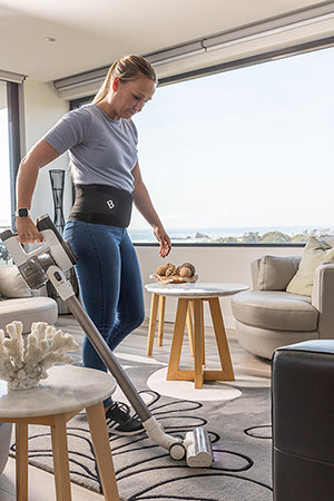 Woman vacuuming while wearing a Bio Magnetic Back Support for stability.