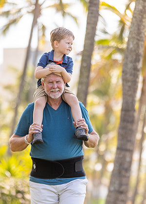 Elderly Man carrying grandson on his shoulders while wearing a Bio magnetic Back brace for support.