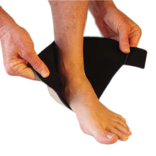 Load image into Gallery viewer, The Bio Magnetic Ankle Support in beige being put on by a person. The magnetic ankle support has been cupped around the ball of the foot and the person is holding the adhesive closure. This is step one of the how to wear process for the magnetic ankle support.