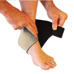 Step 2 in the process of how to wear for the magnetic ankle support. A person has secured the magnetic ankle support around the heal of their foot and are now beginning to wrap the magnetic ankle support across the top of their foot.