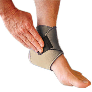 A person has put on the bio magnetic ankle support in beige, they are using their hand to press down on the adhesive closure in the last step to secure the magnetic ankle support around their ankle.