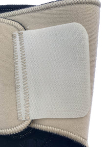 The Bio Magnetic Knee Support in beige up close showing the back of the upper adhesive tab that holds the support in place.