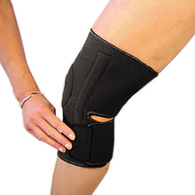Load image into Gallery viewer, The last step in fastening the bio magnetic knee support in black. The bottom strap is being secured into place just below the knee cap on the left side.