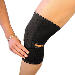 The last step in fastening the bio magnetic knee support in black. The bottom strap is being secured into place just below the knee cap on the left side.