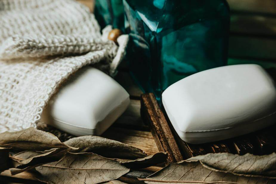 Two bars of white soap among some dried leaves