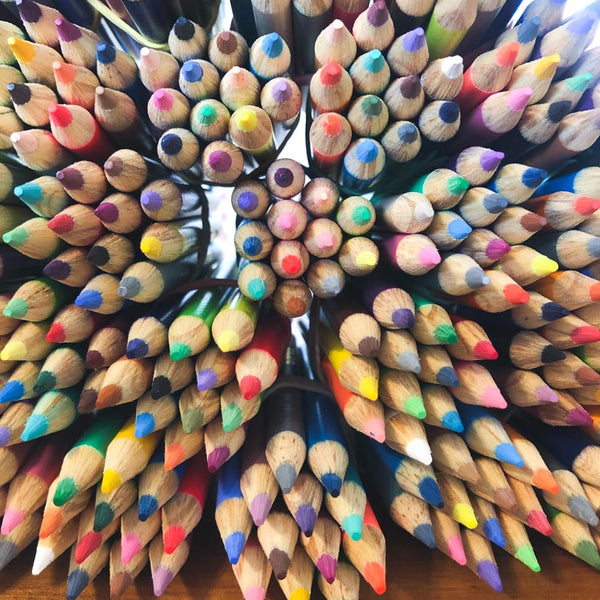 Colored pencil bundles being put together for zine-making kits.