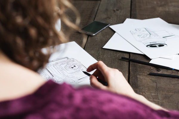 ic: a person drawing a picture on a wooden table