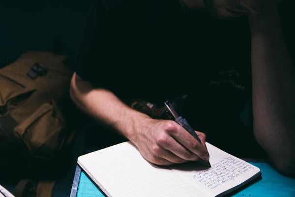 ic: a person writing with a pen in their journal