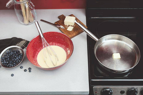 ic: Making pancakes with a skillet, stovetop and blueberries