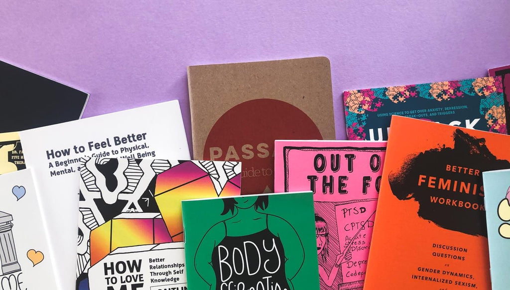 Colorful body image and mental health zines displayed on a purple background.