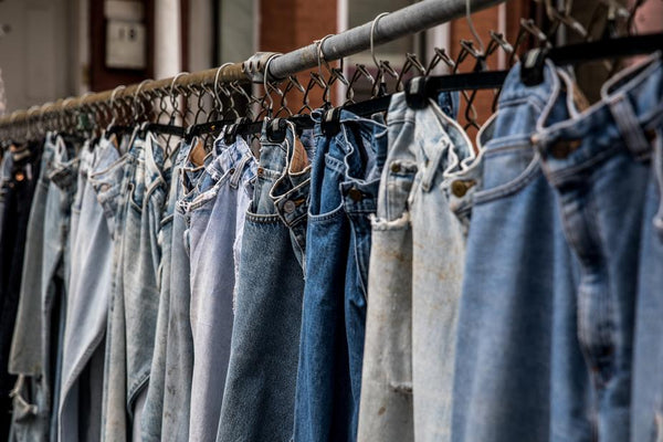 ic: Vintage denim jeans hanging on a thrift store rack.
