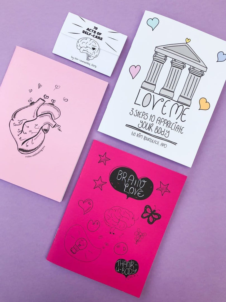 4 zines displayed on a flat surface used to support self care, positive body image, and mental health.