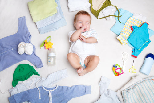 infant surrounded by baby clothes