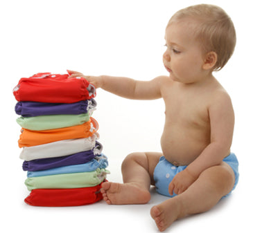 infant next to stack of cloth diapers