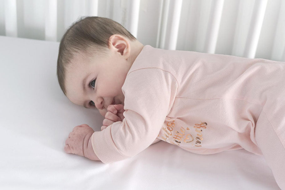 newborn with pacifier in crib
