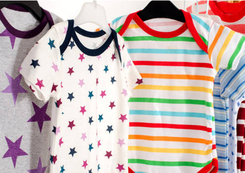 onesies with colorful patterns on hangers