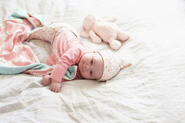smiling infant on bedding