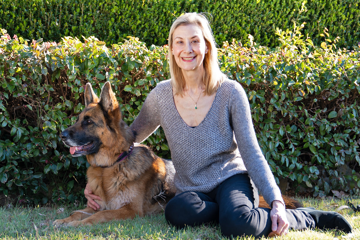 Maddie the German Shepherd and Imola Novak, Style Hound Australia Owner, sitting in front of a hedge