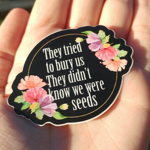 Image shows a black vinyl sticker held in someone's palm. The sticker has a gold circle with pink and purple flowers on two opposite sides. Inside the circle are the words