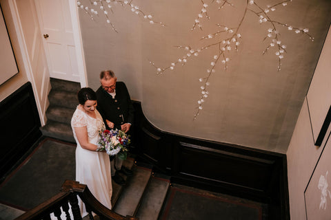 Bride walking down staircase at Thorpe Manor