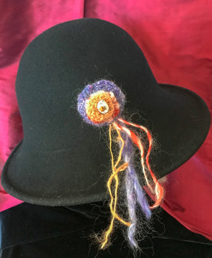 "This brooch is handspun, dyed and then crocheted, stitched and adorned with a bead. Attached to the back is a bar pin. Contents: wool and angora with ceramic and glass beadColors: orange, purple, white, and redSize: 2 1/4"" round x 6 1/2"" longNotes: The pin or brooch can be worn on a hat, scarf, sweater or coat."