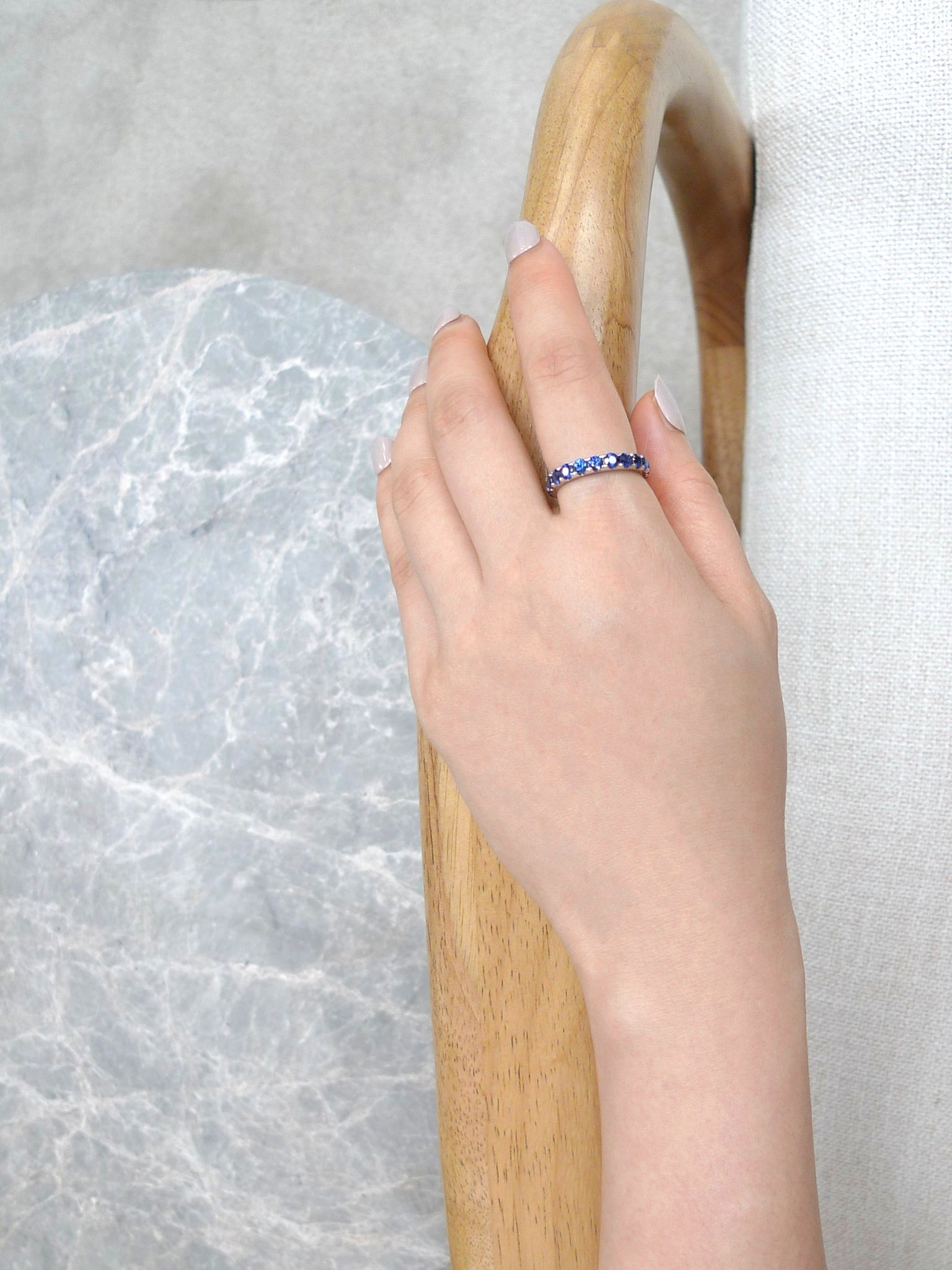 blue_sapphire_half_eternity_wedding_ring_model_hand