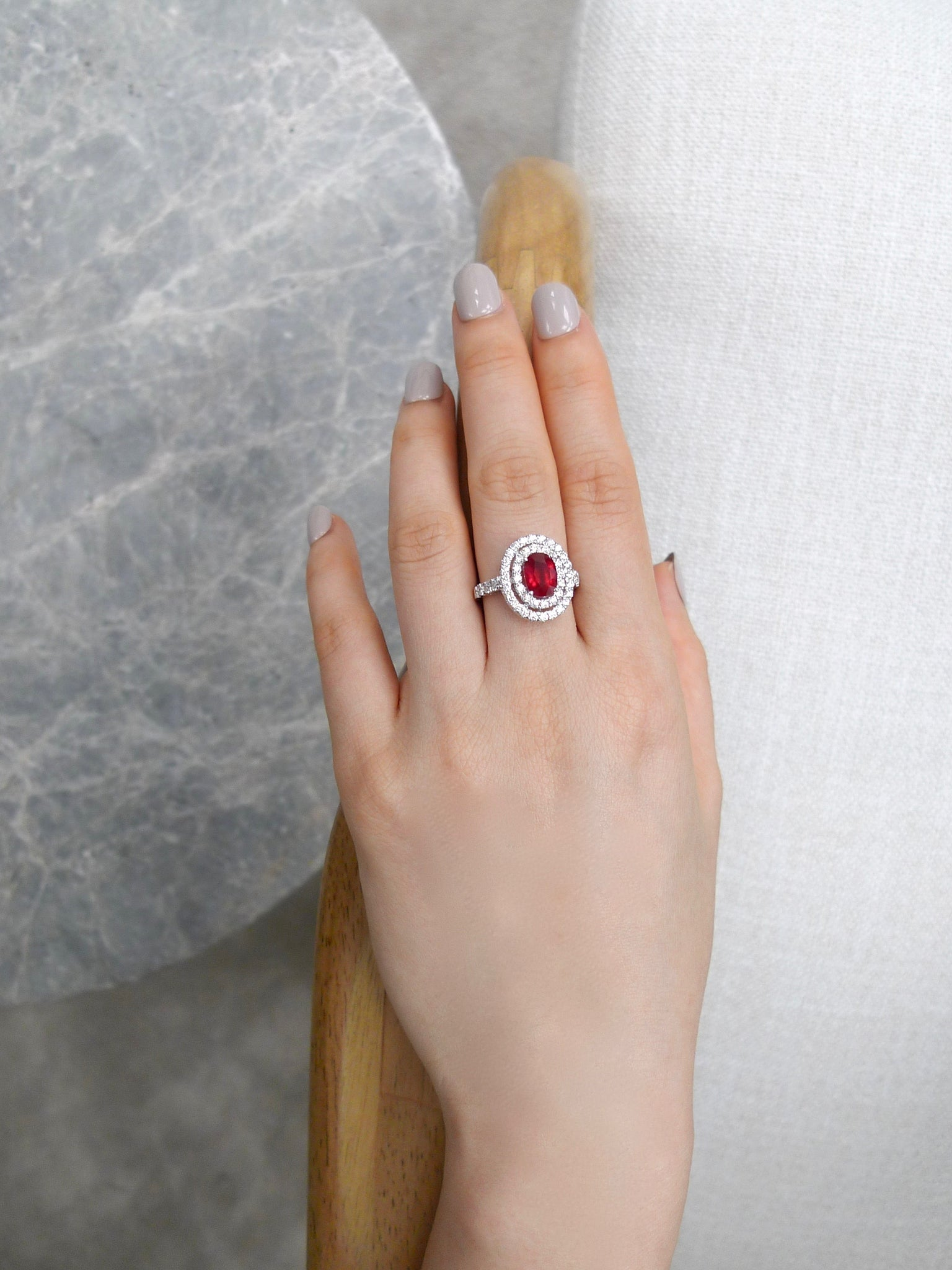 double_halo_diamond_burma_oval_cut_ruby_ring_white_gold_on_model_hand