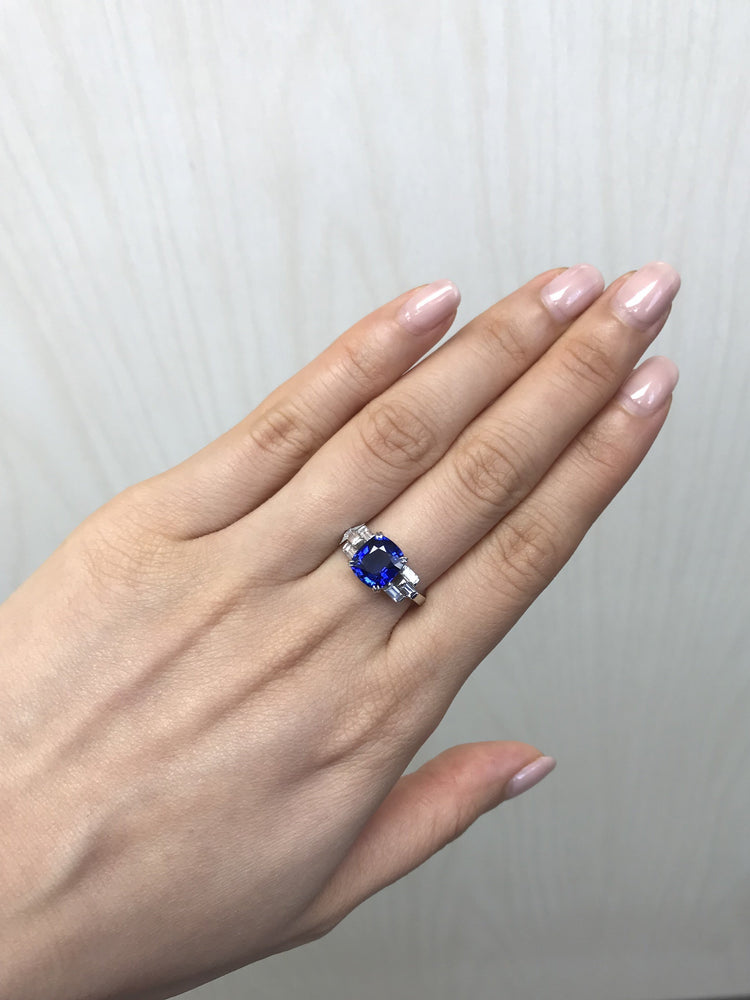 cushion_cut_blue_sapphire_bagguate_diamond_engagement_ring_on_model_hand