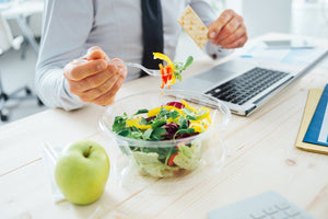 businessman eating healthily with salad, apple and crackers
