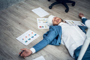 businessman sleeping on floor next to business reports and charts