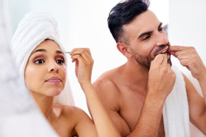 couple getting ready together in bathroom mirror