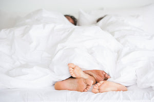 cozy couple sleep routine with feet sticking out from covers