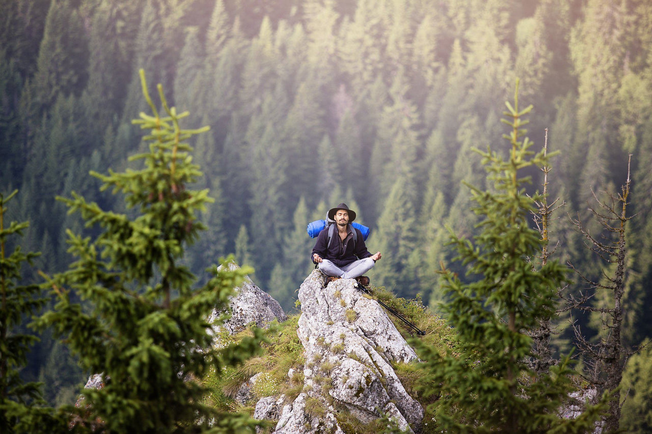 hiker meditating on rock to calm racing thoughts at night