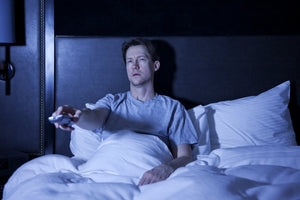 A man watches tv before bed, mixing electronics and sleep