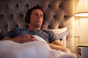 man listening to podcast in bed