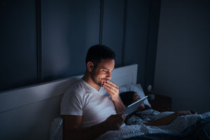 man who can't sleep using tablet at night in bed