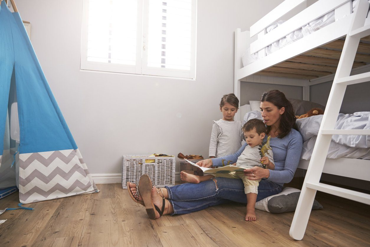 mother reading book to young children next to bunk beds
