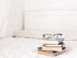 stack of books and eyeglasses on bed with perfect pillows