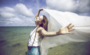 woman enjoying benefits of lucid dreaming by the ocean