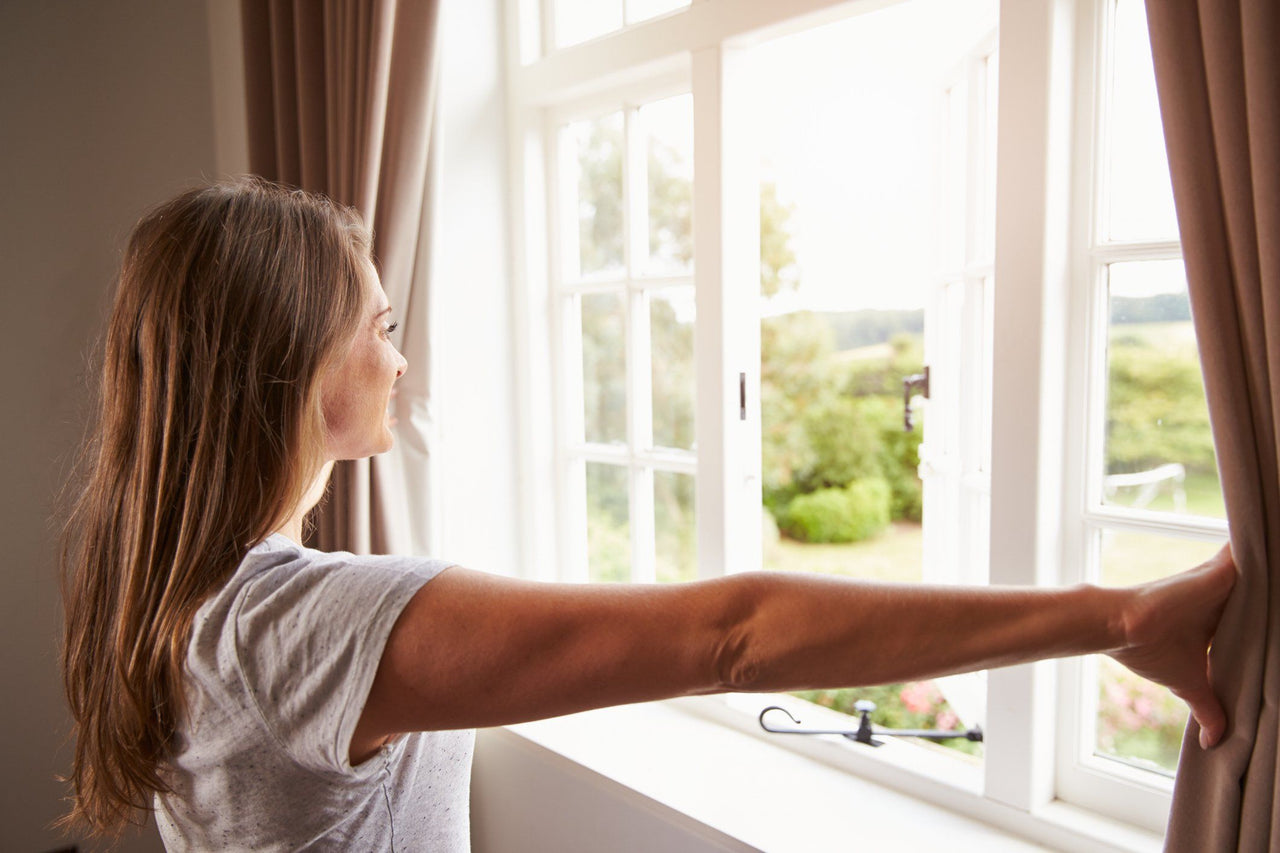 woman opening bedroom curtains looking out open window