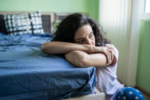 woman worried by bed suffering from sleep dread